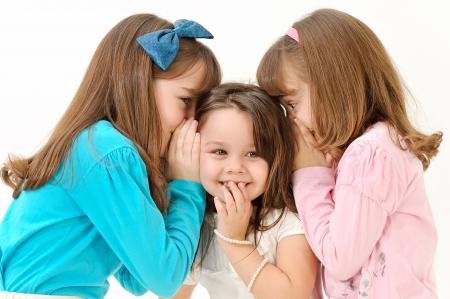 meisjes vertellen van een geheim en het uiten van verrassing op wit wordt geïsoleerd