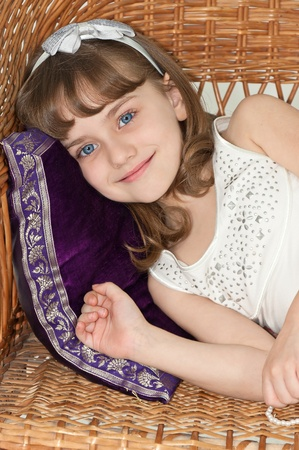 Little girl on sofa on white background photo
