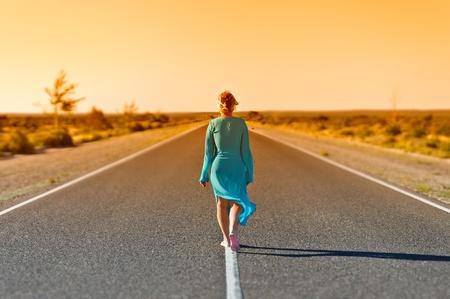 Vrouwen lopen ver weg op de landelijke weg in de zomer dag