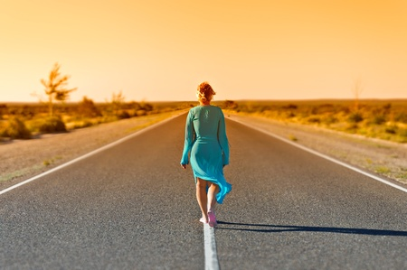 Women walking far away on rural road in summer day photo