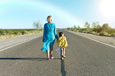 Mother and daughter are walking far away on rural road in summer day photo