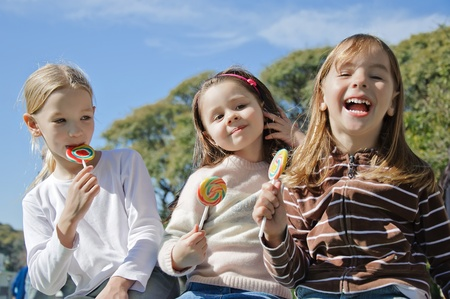 Three sisters sitting in a park eating lollipop suckers Stock Photo - 11781228