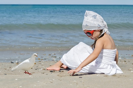 Little girl with dove sitting on the beach photo