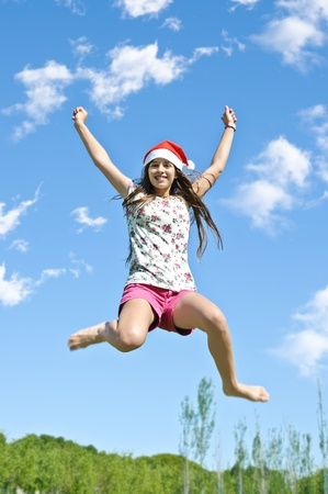 beautiful girl jumping in the park no sky background with santa hat  photo