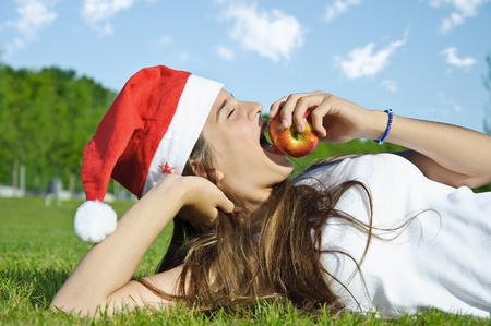 Girl in Santa claus red hat lying on a grass and eat apple photo