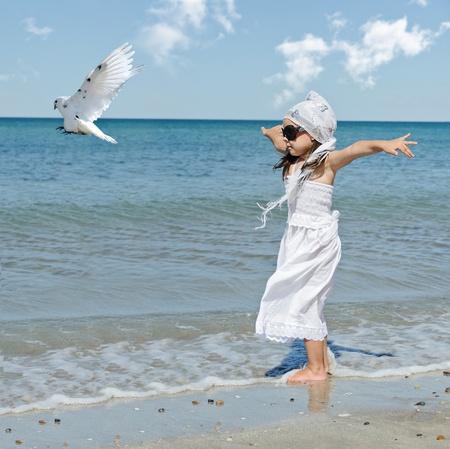 Kleines Mädchen mit Taube sitzt am Strand