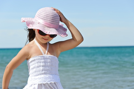 Little girl on the beach wearing funny hat. Stock Photo - 11849571