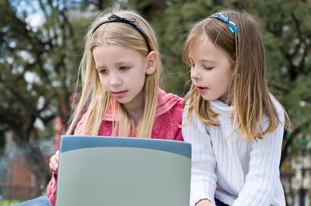 two sisters in park with laptop  photo