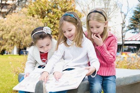 Three sisters sitting on a park reading book Stock Photo - 11849928