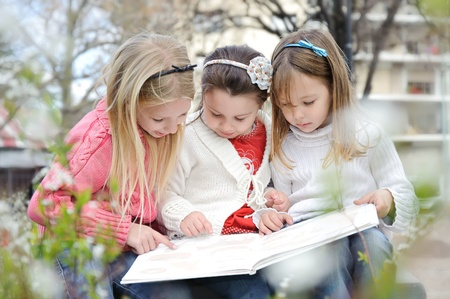 Three sisters sitting on a park reading book