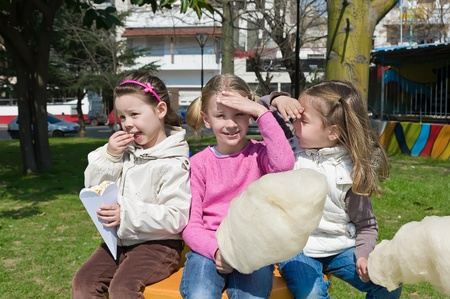 little girls eating candy-floss in the park photo