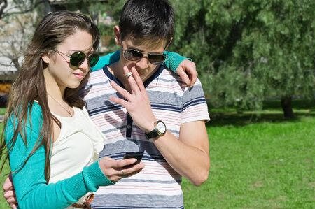 portrait of a young man and a woman with a cigarette and a telephone in the park  photo