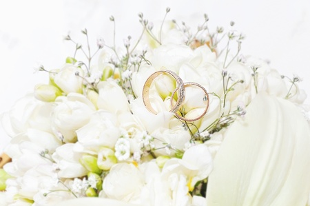 amongst: Wedding Rings sitting in amongst a group of pretty flowers Stock Photo