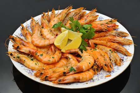Grilled shrimp with parsley and lemon black background photo