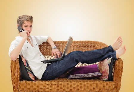 young man on cell phone in front of laptop photo