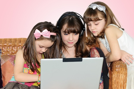 three little girl in headphones with laptop photo