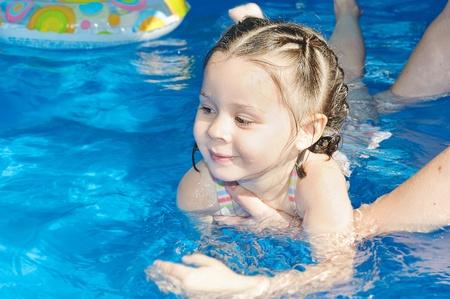 het onderwijzen van schattig meisje hoe om te zwemmen in een zwembad. Kind plezier maken in water met moeder.