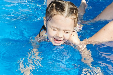 het onderwijzen van schattig meisje hoe om te zwemmen in een zwembad. Kind plezier maken in water met moeder Stockfoto