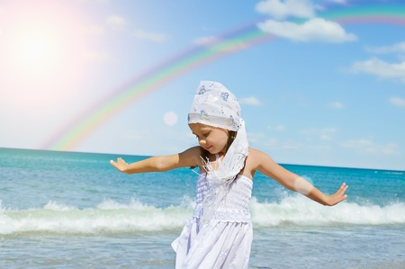 Girl on the beach with handkerchief place with rainbow in background photo
