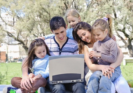 Family in park studying the laptop photo