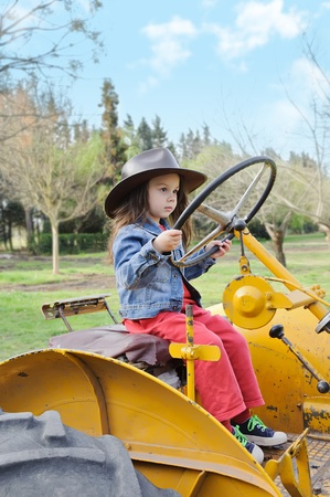 Little girl sitting in an old tractor photo