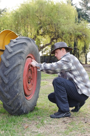Handsome next to a tractor wheel fixing photo