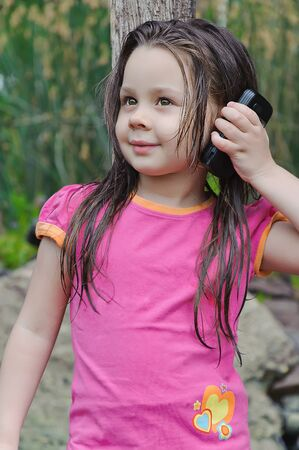 little girl talking to a cell phone Stock Photo - 11849723