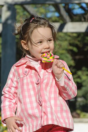 Beautiful girl with the lollipop in the park Stock Photo - 14096378