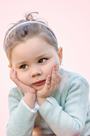 Adorable little girl isolated on soft pink background photo