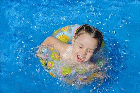 klein meisje zwemmen in een zwembad.