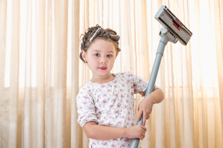 Young Girl with a vacuum cleaner in her room photo