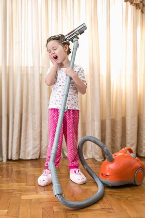 beautiful little girl tired to clean with vacuum aspiration Stock Photo - 14096365