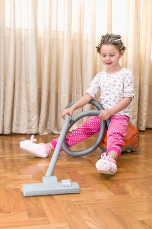 lovely beautiful girl helping mother to clean the room - sitting on the vacuum cleaner photo