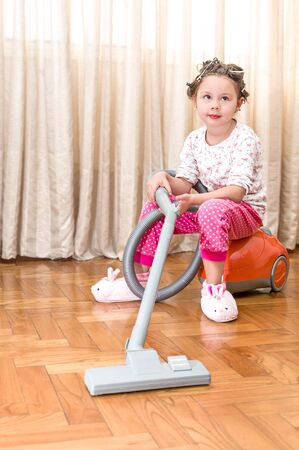 Little girl helping mother to clean the room - sitting on the vacuum cleaner photo