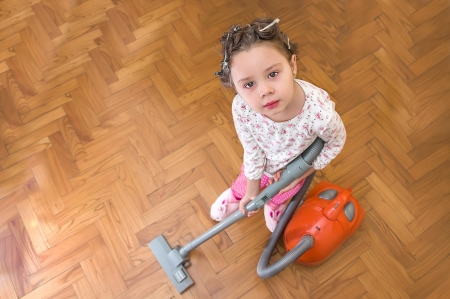 beautiful little girl with vacuum cleaner photo