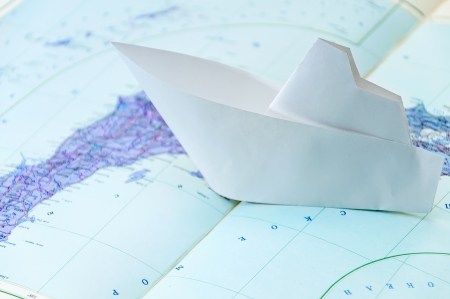 paper boat on top of the world map photo