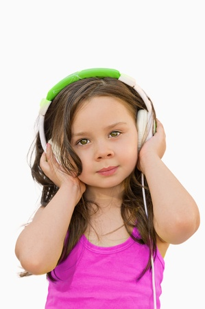 beautiful little girl with headphones listening to music photo