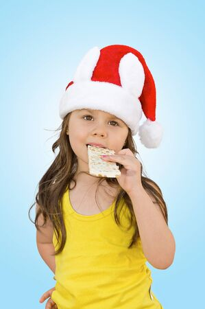 Little girl wearing red Santa hat eating white chocolate with peanuts photo