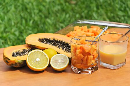Composition of tropical fruit with a mean papaya, lime, orange and glass of fresh juice photo