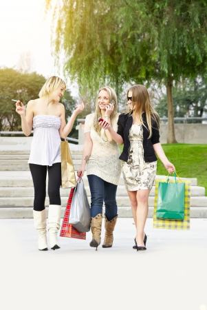 group of friends smiling with shopping bags in the park photo