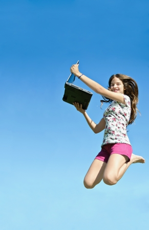 beautiful girl holding a laptop computer jumping over blue sky photo
