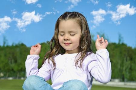 beautiful young girl doing yoga exercise outdoors