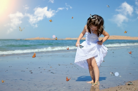 beach butterfly: beautiful adorable girl with butterfly on the beach