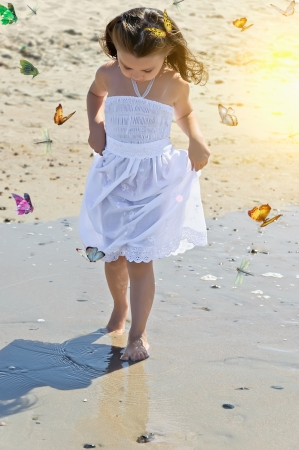 Girl on the beach and butterflies flying around photo
