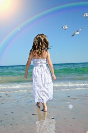 schoonheid meisje loopt strand wal opspattend water in blauwe zee Stockfoto
