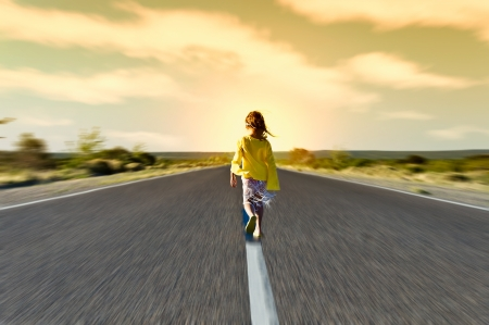 beautiful little girl walking along a road paved by the tardecer Stock Photo