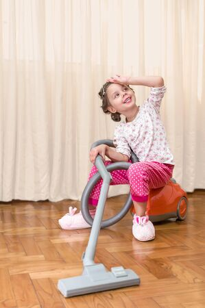 Beautiful little girl helping mother to clean the room - sitting on the vacuum cleaner photo