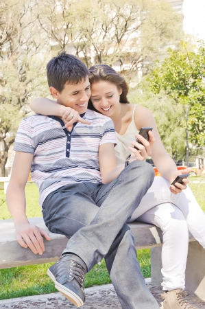 2 november: Portrait of romantic young couple in autumn outdoor with mobile phone Stock Photo