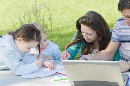 children draw with mother in a park photo