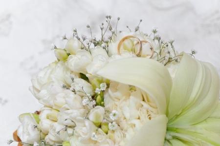 Trouwringen zitten te midden van een groep van mooie bloemen Stockfoto - 14835078